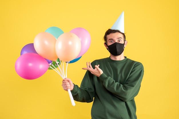 Vooraanzicht jonge man met feestmuts en zwart masker wijzend op ballonnen op geel