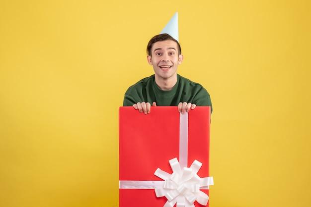 Vooraanzicht jonge man met feestmuts staande achter grote geschenkdoos op gele achtergrond