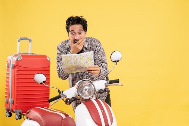 Vooraanzicht jonge man met fiets observeren kaart met geschokte uitdrukking op geel