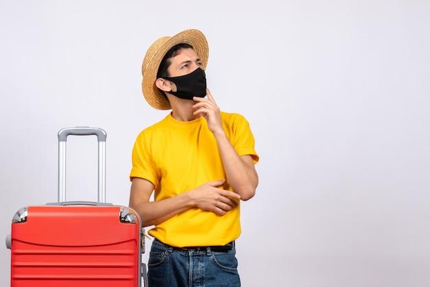 Vooraanzicht jonge man met geel t-shirt en rode koffer denken