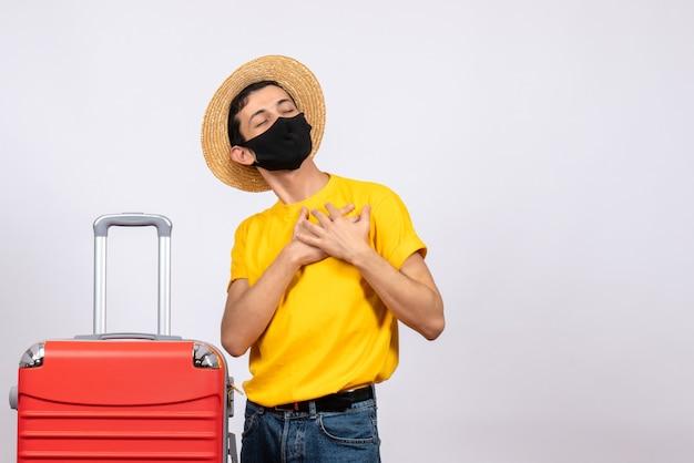 Vooraanzicht jonge man met geel t-shirt en rode koffer handen op zijn borst