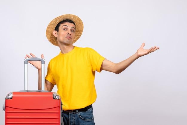 Vooraanzicht jonge man met geel t-shirt en rode koffer
