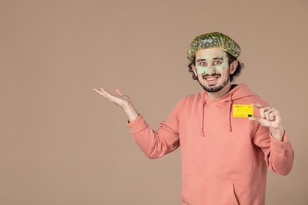 Vooraanzicht jonge man met gele creditcard op bruine achtergrond huid huidverzorging gezichtsverzorging spa geldtherapie