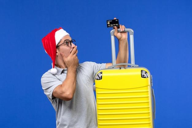 Vooraanzicht jonge man met gele zak bankkaart op een blauwe achtergrond reis vakantie emoties
