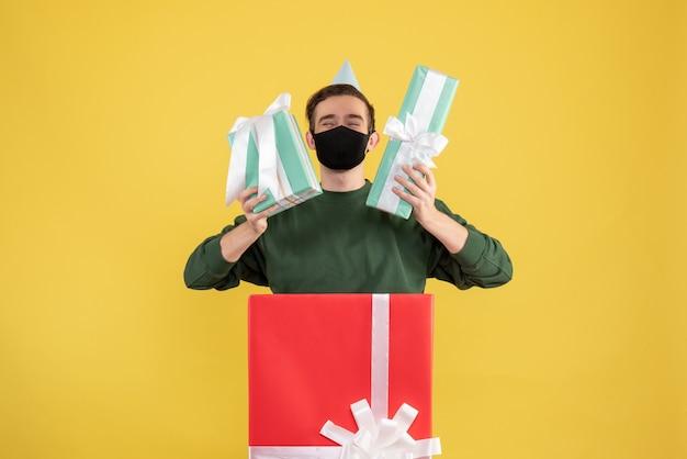 Vooraanzicht jonge man met geschenkdozen staan achter grote geschenkdoos op geel