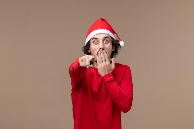 Vooraanzicht jonge man met geschokt gezicht op bruine achtergrond vakantie emoties kerstmis
