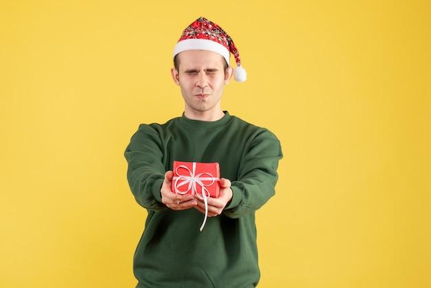 Vooraanzicht jonge man met gesloten ogen geschenk op geel te houden