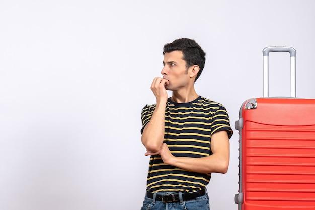 Vooraanzicht jonge man met gestreepte t-shirt en koffer verwarrend