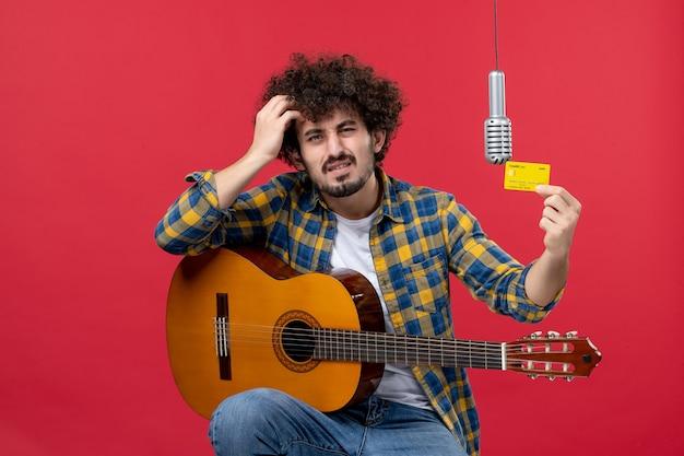 Vooraanzicht jonge man met gitaar met bankkaart op een rode muur band zanger live optreden muzikant concert geld kleur
