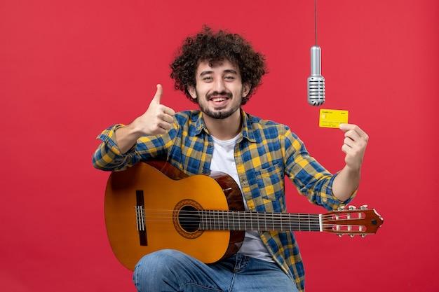 Vooraanzicht jonge man met gitaar met bankkaart op rode muurband zanger live optreden muzikant geldkleur