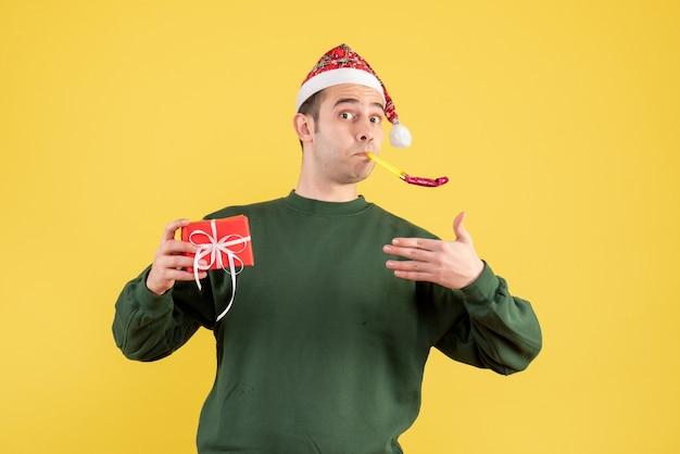 Vooraanzicht jonge man met groene trui met behulp van noisemaker staande op geel