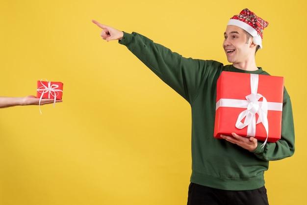 Vooraanzicht jonge man met groene trui wijzend op iets staande menselijke hand met geschenk op geel