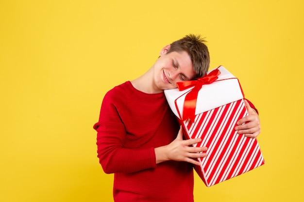 Vooraanzicht jonge man met grote kerst aanwezig op een geel