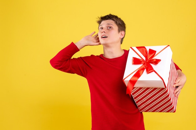 Vooraanzicht jonge man met grote kerst aanwezig op gele achtergrond