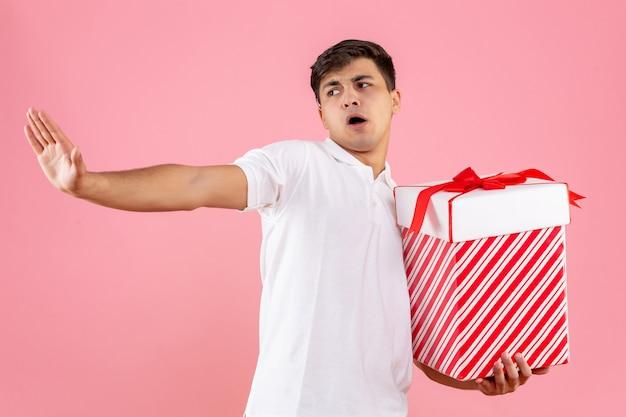 Vooraanzicht jonge man met grote kerstcadeautjes op roze achtergrond