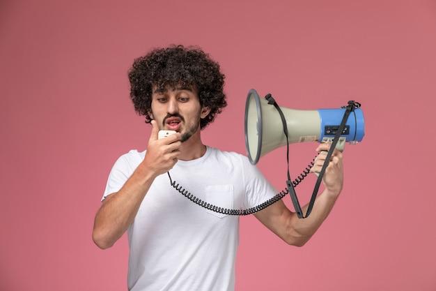 Vooraanzicht jonge man met hand microfoon in wit t-shirt
