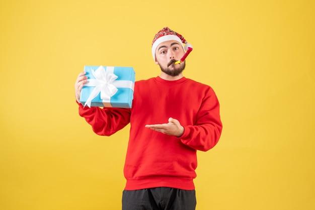 Vooraanzicht jonge man met kerst aanwezig op gele achtergrond