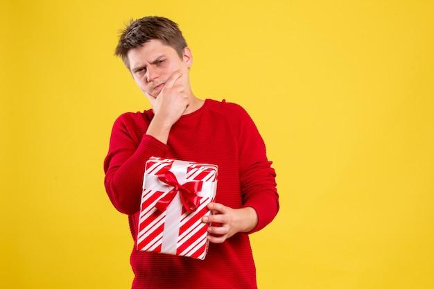 Vooraanzicht jonge man met kerst aanwezig op gele vloer cadeau