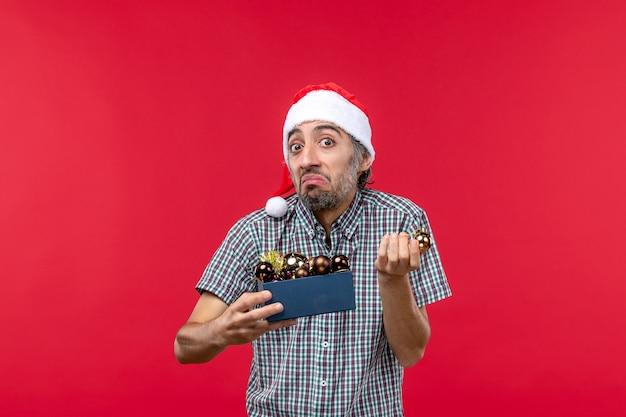 Vooraanzicht jonge man met kerstboom speelgoed op rood bureau