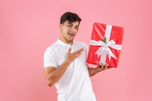 Vooraanzicht jonge man met kerstcadeau op roze achtergrond