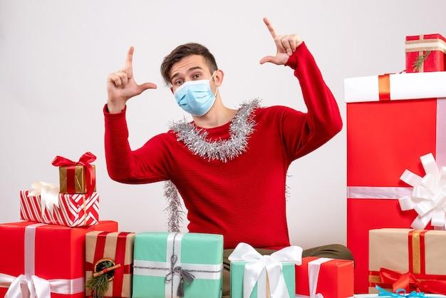 Vooraanzicht jonge man met kerstcadeaus rondhangen op witte achtergrond Gratis Foto