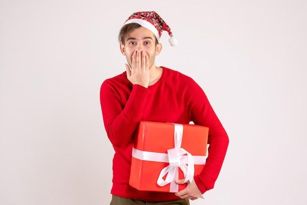 Vooraanzicht jonge man met kerstmuts die zijn mond op een witte achtergrond
