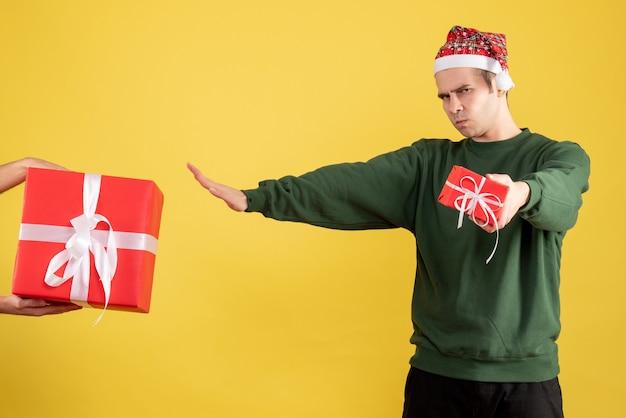Vooraanzicht jonge man met kerstmuts het geschenk in vrouwelijke hand op gele achtergrond