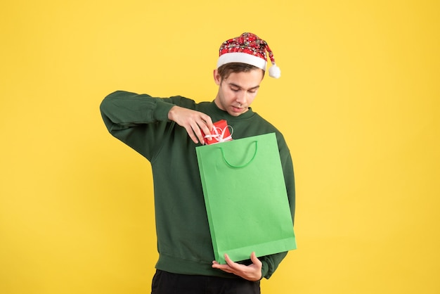 Vooraanzicht jonge man met kerstmuts met groene boodschappentas en cadeau staande op gele achtergrond kopie ruimte