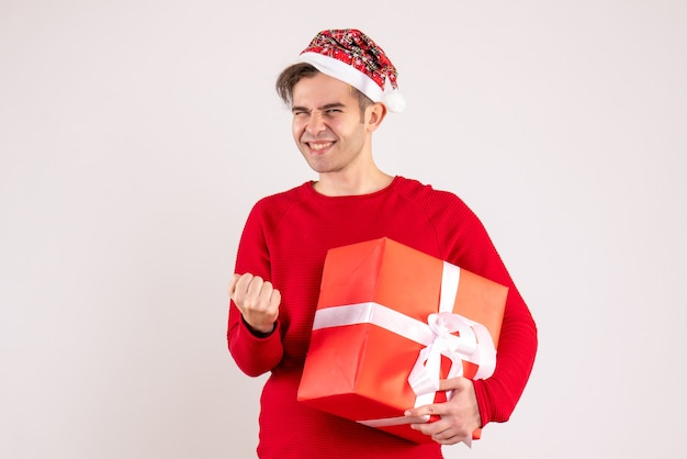 Vooraanzicht jonge man met kerstmuts met winnende gebaar op witte achtergrond