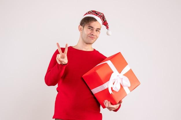 Vooraanzicht jonge man met kerstmuts overwinning teken maken op witte achtergrond