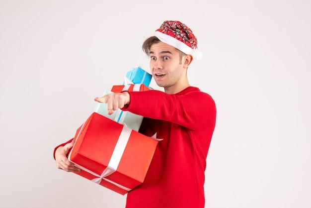 Vooraanzicht jonge man met kerstmuts staande op een witte achtergrond kopie ruimte