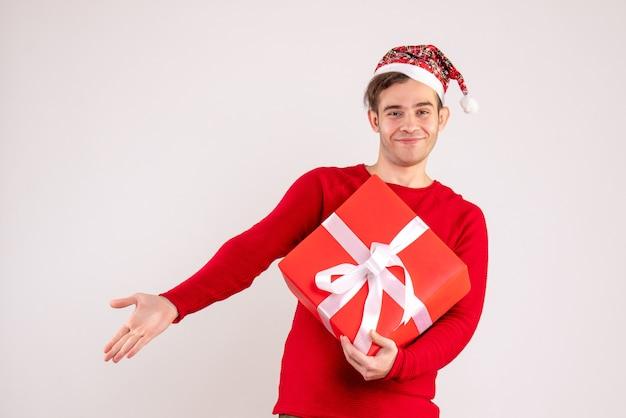 Vooraanzicht jonge man met kerstmuts staande op een witte achtergrond met vrije ruimte