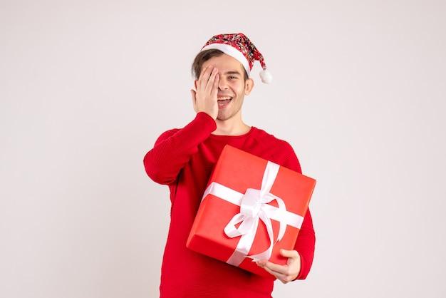 Vooraanzicht jonge man met kerstmuts staande op een witte achtergrond