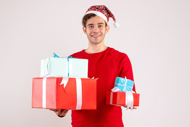 Vooraanzicht jonge man met kerstmuts staande op witte achtergrond vrije ruimte