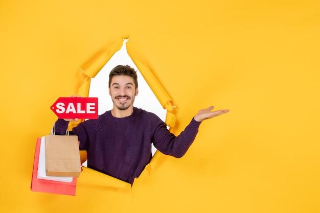 Vooraanzicht jonge man met kleine pakjes en verkoop schrijven op gele achtergrond cadeau kleur kerstvakantie foto winkelen