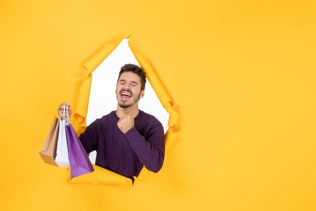 Vooraanzicht jonge man met kleine pakjes na het winkelen op gele achtergrond cadeau nieuwjaar aanwezig kerstvakantie