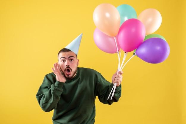 Vooraanzicht jonge man met kleurrijke ballonnen op een gele achtergrond