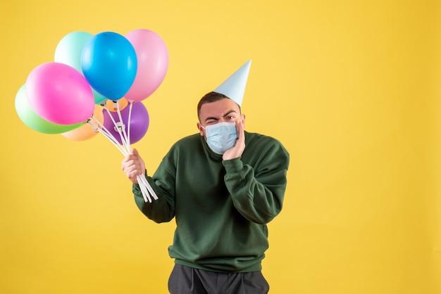 Vooraanzicht jonge man met kleurrijke ballonnen op een gele achtergrond Gratis Foto