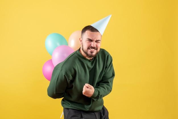 Vooraanzicht jonge man met kleurrijke ballonnen op gele achtergrond