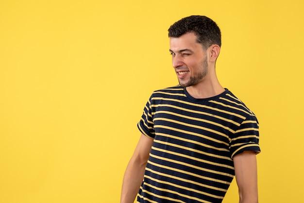 Vooraanzicht jonge man met knipperende ogen staande op gele geïsoleerde achtergrond