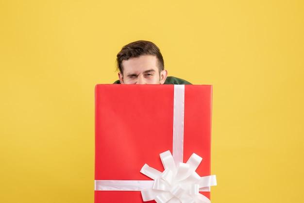 Vooraanzicht jonge man met knipperende ogen verstopt achter grote geschenkdoos op geel