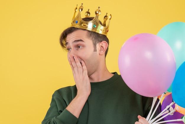 Vooraanzicht jonge man met kroon en zwart masker hand aan zijn mond op geel