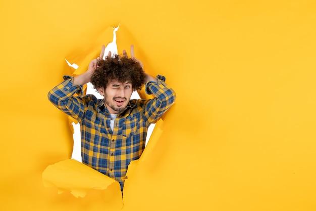 Vooraanzicht jonge man met krullend haar knipogend op gele gescheurde achtergrond