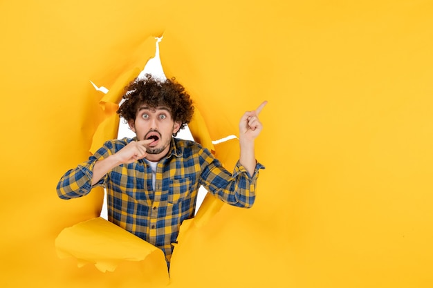 Vooraanzicht jonge man met krullend haar op gele gescheurde achtergrond