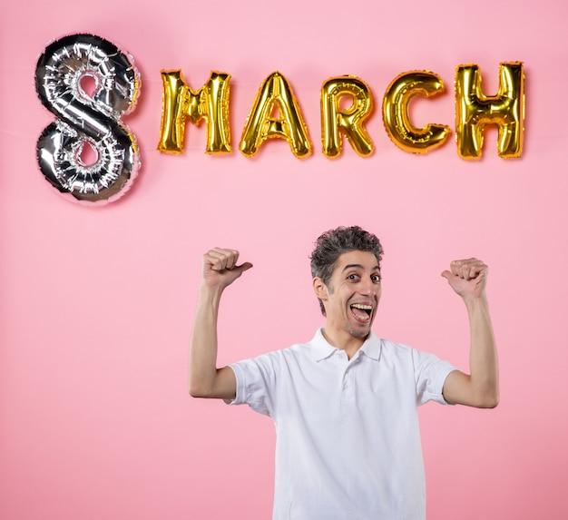 Vooraanzicht jonge man met maart decoratie op roze achtergrond kleur vakantie sensueel gelijkheid model emotie vrouwendag feest