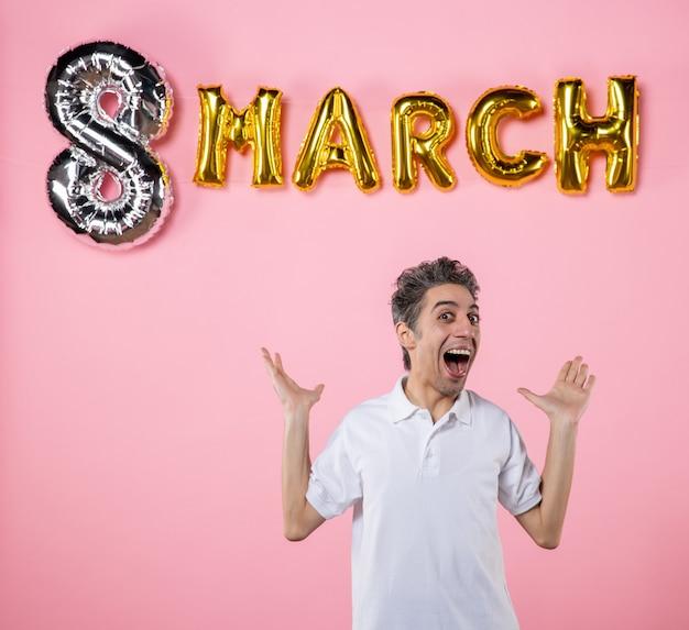 Vooraanzicht jonge man met maart decoratie op roze achtergrond kleur vakantie sensueel gelijkheid model emotie vrouwendag