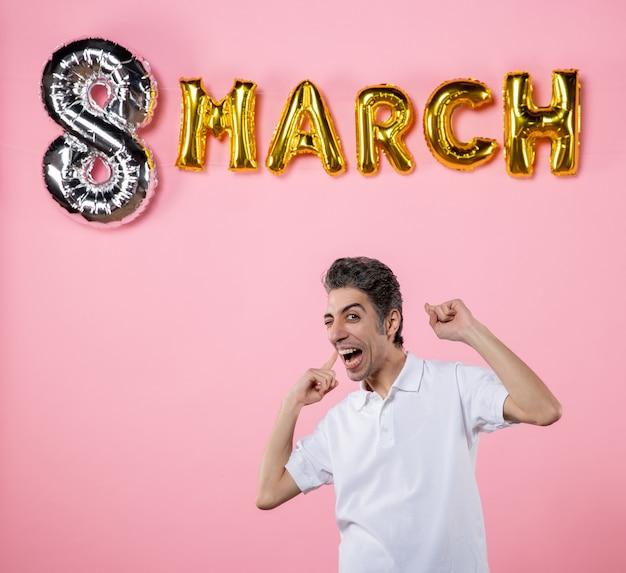Vooraanzicht jonge man met maart decoratie op roze achtergrond kleur vakantie sensueel gelijkheid model emoties vrouwendag feest