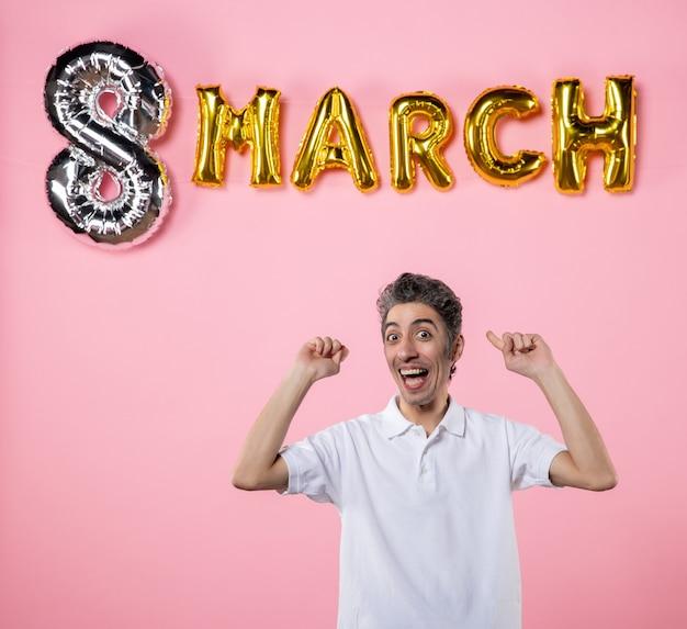 Vooraanzicht jonge man met maart decoratie op roze achtergrond kleur vakantie sensuele gelijkheid emotie vrouwendag feest