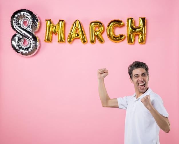 Vooraanzicht jonge man met maart decoratie op roze achtergrond kleur vakantie vrouwen dag vrouwelijke emotie gelijkheid sensuele party
