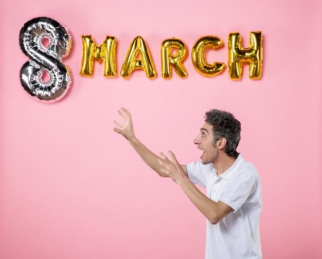 Vooraanzicht jonge man met maart decoratie op roze achtergrond vakantie glamour vrouwen dag feest vrouwelijke emotie gelijkheid sensueel
